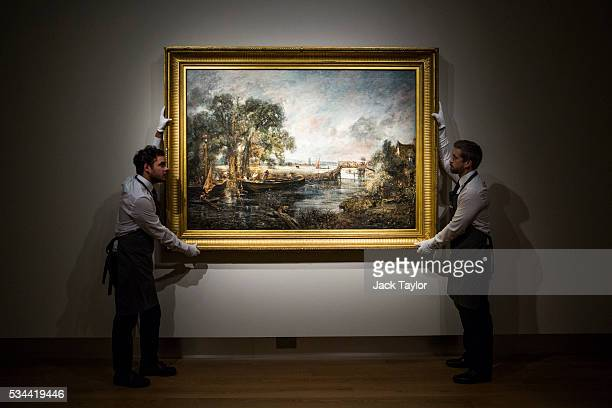 Christie's employees pose with 'View on the River Stour near Dedham' circa 1821-1822 by English painter John Constable at the auction house on May...