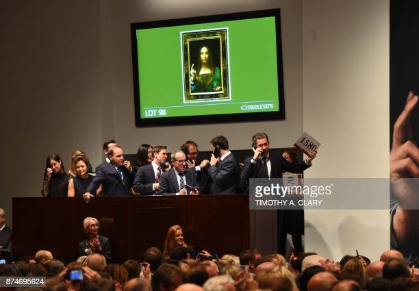 Christie's employees take bids for Leonardo da Vincis Salvator Mundi at Christie's New York November 15 2017 A 500yearold work of art depicting Jesus...