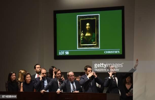 Christie's employees take bids for Leonardo da Vincis 'Salvator Mundi' at Christie's New York on November 15 2017 A 500yearold work of art depicting...