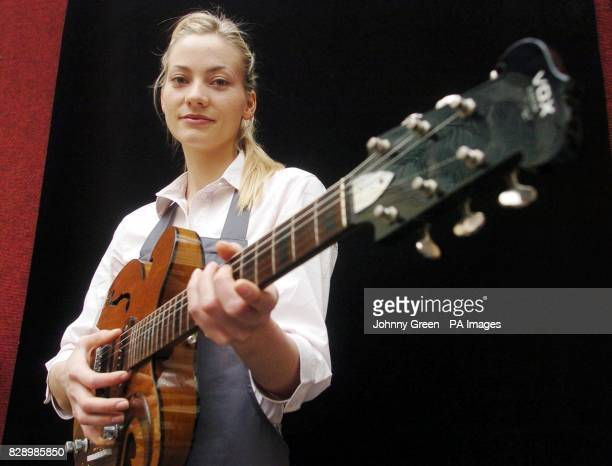 Christie's intern Annika Murjahn from Freiburg in Germany picks up a custommade Vox Kensington guitar given to Alex Mardas by John Lennon at a...