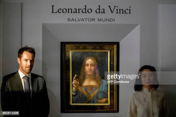 Christies representatives pose after Leonardo da Vinci's 'Salvator Mundi' painting was unveiled in Hong Kong on October 13 2017 / AFP PHOTO / Anthony...