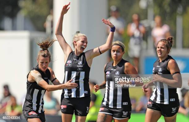 Christina Bernardi of the Magpies is congratulated by Moana Hope of the Magpies and her teammates after kicking a goal during the round six AFL...