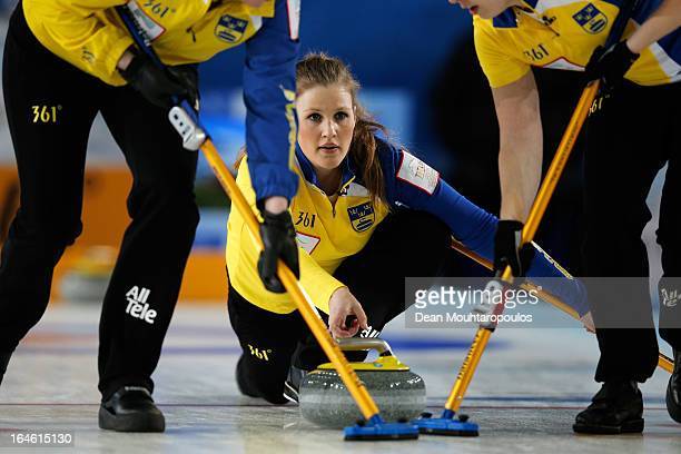 Christina Bertrup of Sweden throws a stone as Maria Prytz and Maria Wennerstrom sweep during the Gold Medal match between Scotland and Sweden on Day...