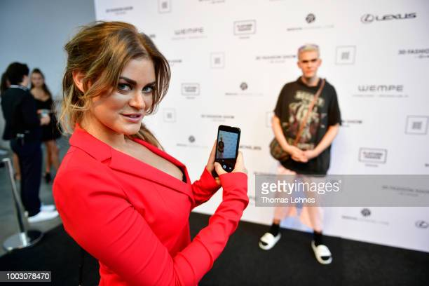Christina Braun takes a photo of Emil Winter as they attend the 3D Fashion Show by Lexus show during Platform Fashion July 2018 at Areal Boehler on...