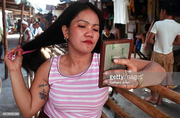 Christina Bunuan combs her hair. She stays with her husband Joey at their barrack in the Manila City Jail. Sputnik is one of 4 major gangs in Manila...