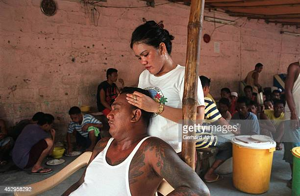 Christina Bunuan gives a massage to her husband Joey at their barrack in the Manila City Jail. Sputnik is one of 4 major gangs in Manila City Jail....