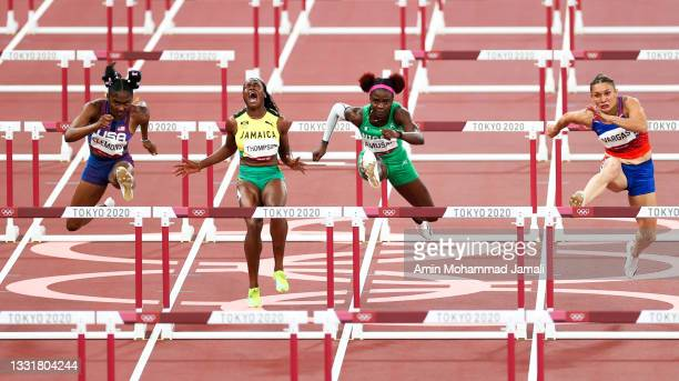 Christina Clemons of Team United States and Tobi Amusan of Team Nigeria leap over a hurdle as Yanique Thompson of Team Jamaica crashes in the Women's...