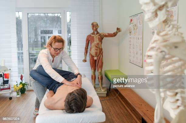 Christina Grosse Boymann, healing practitioner, osteopath and physiotherapist, treating a young man at her practice in Frankfurt an der Oder,...