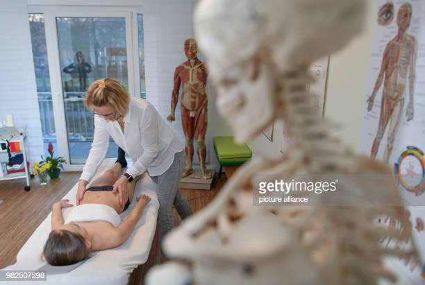 Christina Grosse Boymann, healing practitioner, osteopath and physiotherapist, treating a girl at her practice in Frankfurt an der Oder, Germany, 01...