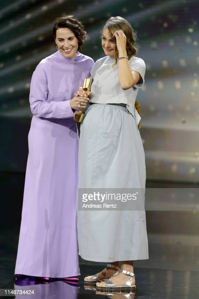 Christina Hecke congratulates Luise Heyer, winner of the best female supporting role award, reacts on stage during the Lola - German Film Award show...