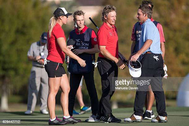 Christina Jason and Bernhard Langer of Germany talk with Tucker Wadkins on the 18th green after the first round of the PNC Father/Son Challenge at...