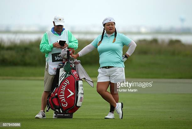 Christina Kim and her caddie stand in the fairway on the third hole during the first round of the ShopRite LPGA Classic presented by Acer on the Bay...