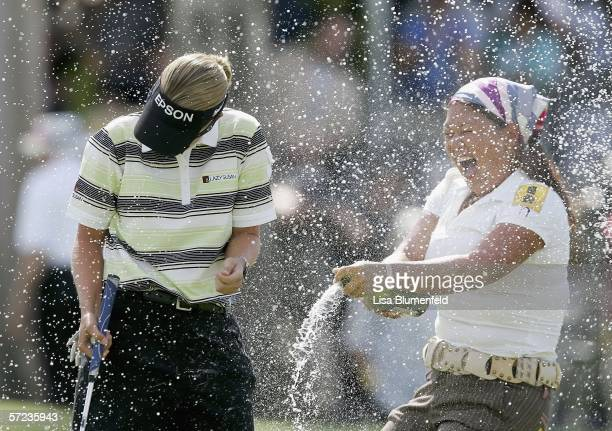 Christina Kim sprays Karrie Webb of Australia with champagne after Webb defeated Lorena Ochoa of Mexico in a sudden death playoff on the 18th hole...