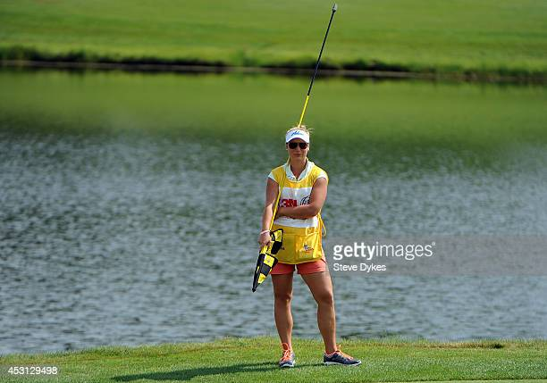 Christina Langer daughter and caddie of Bernhard Langer of Germany waits for her father to putt on the 17th hole during the final round of the 3M...