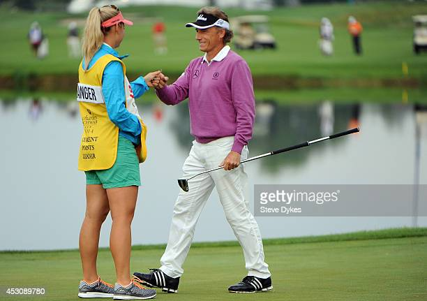 Christina Langer fist bumps her father Bernhard Langer of Germany after he sank a birdie putt on the 18th hole during the second round of the 3M...