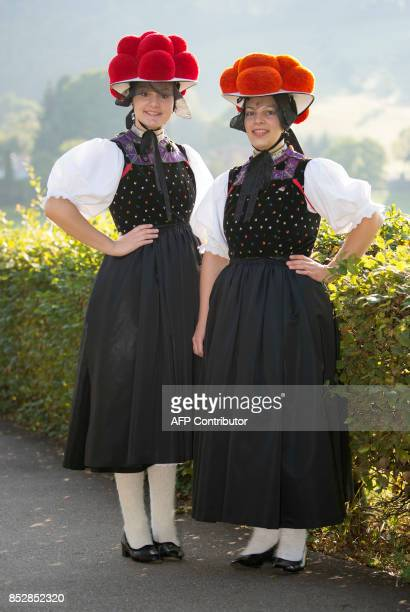Christina Lehmann and Jana Bruestle pose in traditional dresses of the Black Forest region with the red Bollenhut in Gutach southern Germany on...