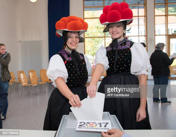 Christina Lehmann and Jana Bruestle wear traditional dresses of the Black Forest area including the typical 'Bollenhut' pompon hats as they cast...