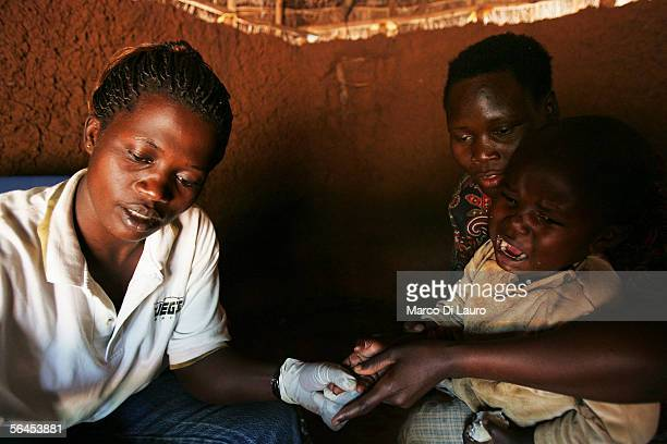 Christina Masete a laboratory technician of the local Aids Information Center collects a sample of blood from the finger of a child to test him for...