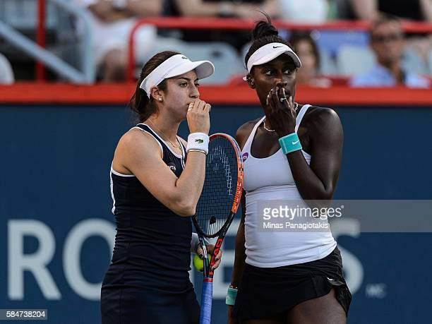 Christina McHale and Asia Muhammad of the United States talk over their strategy against Ekaterina Makarova and Elena Vesnina of Russia during day...