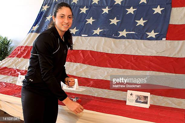 Christina McHale makes a stitch in the National 9/11 Flag on display during the BNP Paribas Open at the Indian Wells Tennis Garden on March 9 2012 in...