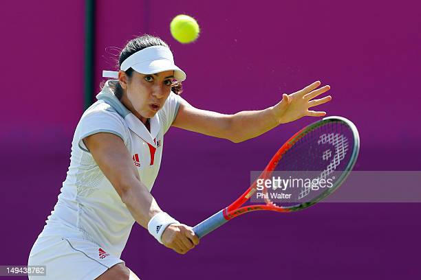 Christina Mchale of the United States return a shot against Ana Ivanovic of Serbia on Day 1 of the London 2012 Olympic Games at the All England Lawn...