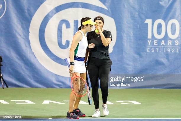 Christina McHale of USA and Sania Mirza of India whisper to each other during the second set of their quarterfinal doubles match against Shuai Zhang...