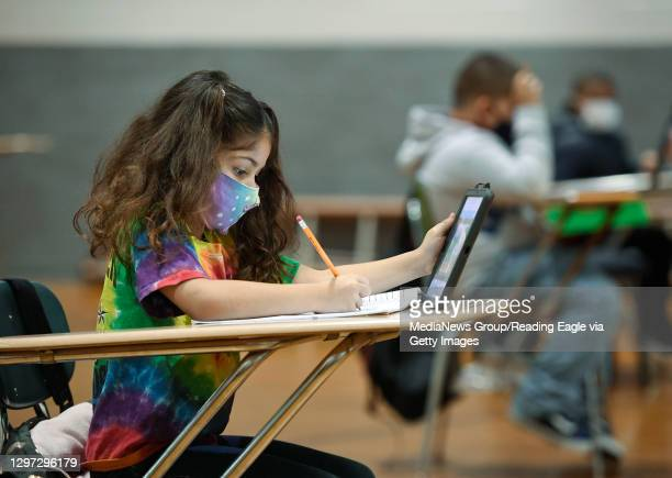 Christina Pagan does her school work using an iPad and a pencil with a workbook. At the Mulberry Street location of the Olivet Boys and Girls Club in...