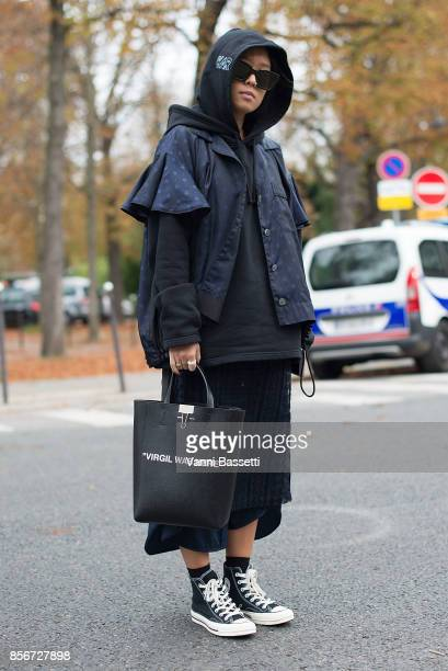 Christina Paik poses wearing Sacai and an Off White bag after the Sacai show at the Grand Palais during Paris Fashion Week Womenswear SS18 on October...