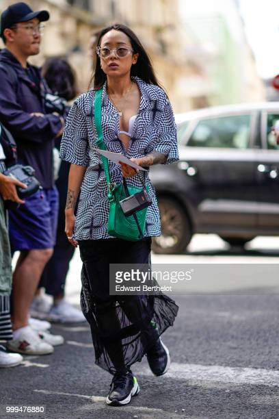Christina Paik wears a green bag a black and white jacket a black lace skirt black sneakers outside Wooyoungmi during Paris Fashion Week Menswear...