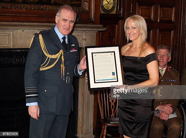 Christina Schmid the widow of British soldier Staff Sergeant Olaf Schmid receives the George Cross citation from Chief of the Defence Staff Air Chief...