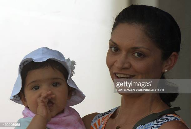 Christina Sirisena wife of Sri Lankan cricketer Mahela Jayawardene holds up their daughter as they watch the first day of the opening Test match...