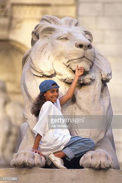 "Christina Vidal poses on a lion statue in June 1993 in front of the New York Public Library in New York City. Vidal played ""Angie Vega"" in the 1993..."