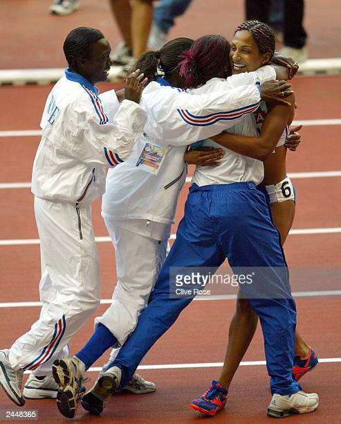 Christine Arron is mobbed by her French teammates after she wins on the anchor leg in the women's 4x100m relay final at the 9th IAAF World Athletics...