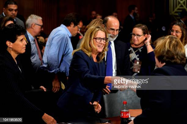 Christine Blasey Ford shakes hands with Phoenix prosecutor Rachel Mitchell as she finished testifying before the Senate Judiciary Committee on...