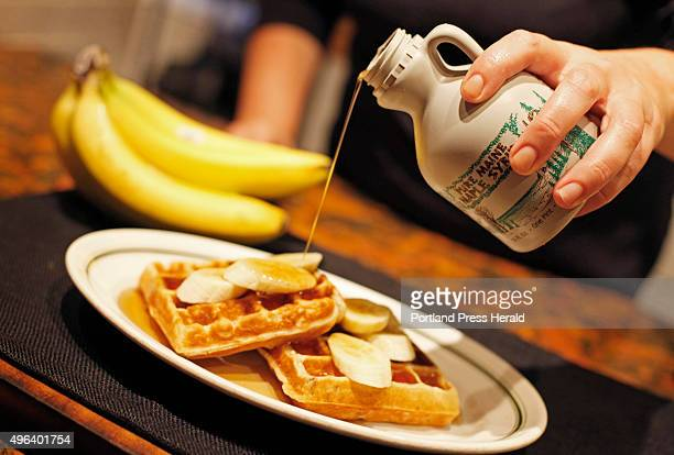 Christine Burns Rudalevige pours pure Maine maple syrup atop home made banana waffles