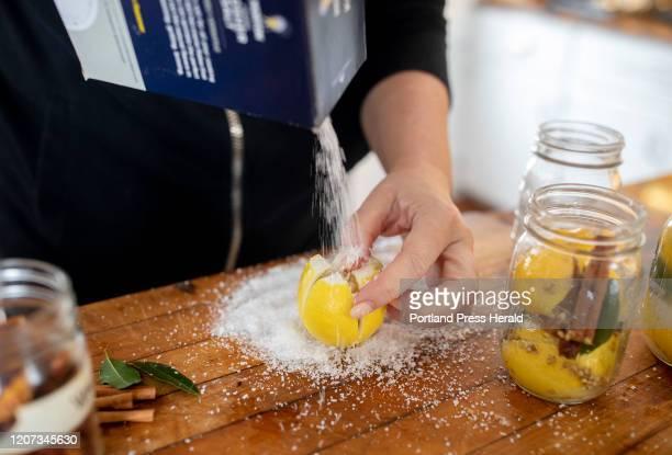 Christine Burns Rudalevige pours salt into a quartered lemon before putting it into a mason jar along with cinnamon sticks bay leaves cloves...