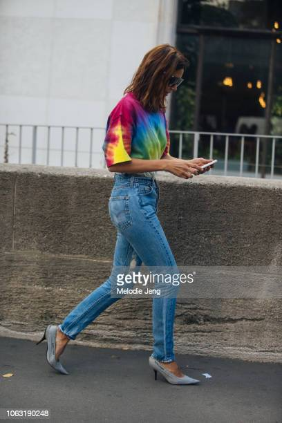 Christine Centenera checks her phone and wears a tie-dye shirt, blue jeans, and gray Balenciaga heels during Paris Fashion Week Spring/Summer 2019 on...