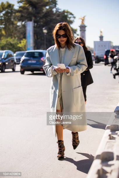 Christine Centenera wearing a white dress white coat and brown heels is seen after the Maison Margiela show on September 26 2018 in Paris France