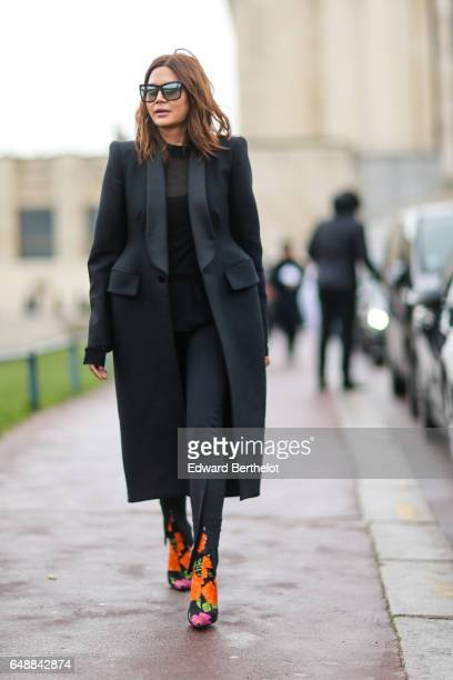 Christine Centenera wears a black coat a lace black top black pants silver sunglasses and flower print boots outside the Hermes show during Paris...
