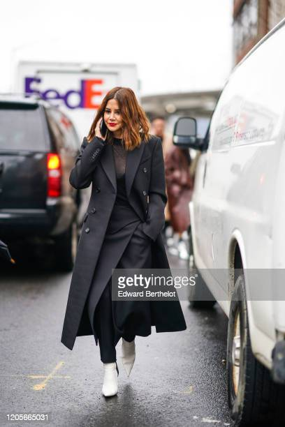 Christine Centenera wears a black long coat a black mesh top a skirt white pointy shoes outside Coach during New York Fashion Week Fall Winter 2020...