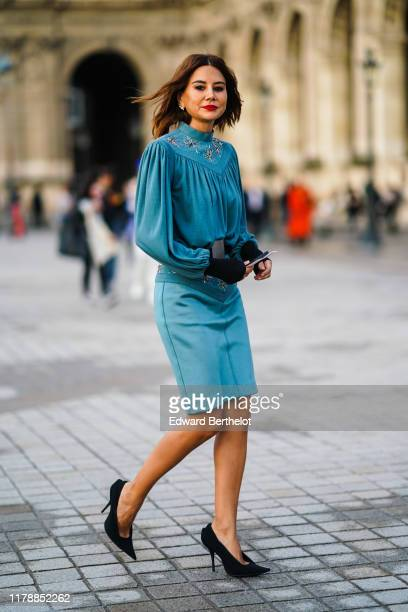 Christine Centenera wears a blue pleated dress with metallic embroidery black shoes a belt outside Louis Vuitton during Paris Fashion Week Womenswear...