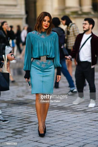 Christine Centenera wears a blue pleated dress with metallic embroidery, black shoes, a belt, outside Louis Vuitton, during Paris Fashion Week -...
