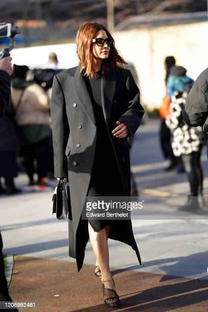 Christine Centenera wears sunglasses a black oversized long coat a black dress during London Fashion Week February 2020 on February 17 2020 in London...