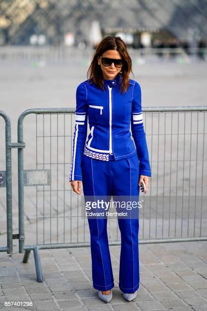 Christine Centenera wears sunglasses a blue jacket blue flare pants gray shoes outside Louis Vuitton during Paris Fashion Week Womenswear...