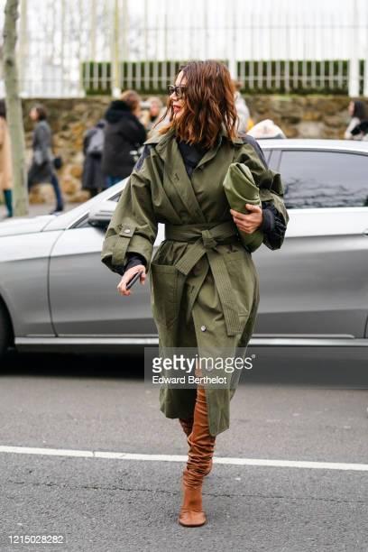 Christine Centenera wears sunglasses, a green khaki long trench coat, a green khaki Bottega Veneta bag, brown high boots, outside Loewe, during Paris...