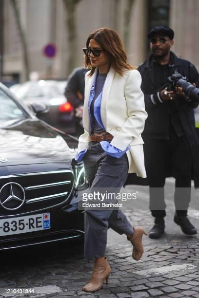 Christine Centenera wears sunglasses, a white jacket, a mauve shirt, a t-shirt, a brown leather belt, gray pants, brown leather shoes, outside Miu...