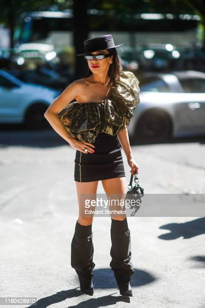 Christine Chiu wears a hat, sunglasses, a golden off-shoulder shiny ruffled top, a black skirt, high boots, a Dior bag, outside Alexandre Vauthier,...