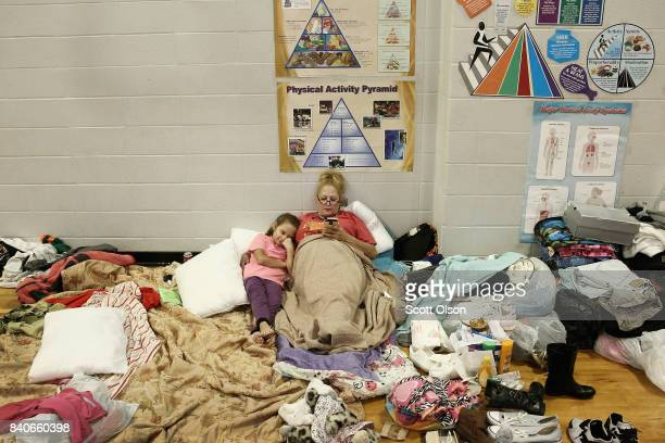Christine Garcia relaxes with her eightyearold daughter Mia in the Channelview High School gym which has been turned in to an evacuation shelter for...