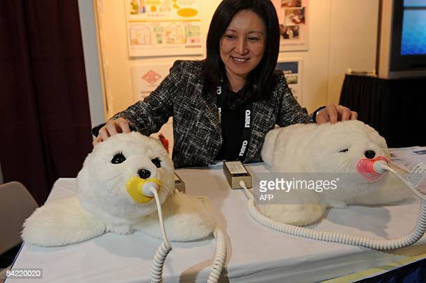 Christine Hsu pets two Paro therapeutic robots on display at the Japan External Trade Organization at the 2009 Consumer Electronics Show in Las Vegas...