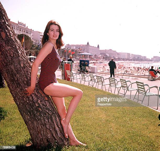 Christine Keeler key figure in the 1963 Profumo Scandal which rocked the government wearing a swimsuit as she leans against a tree on a beach 1963